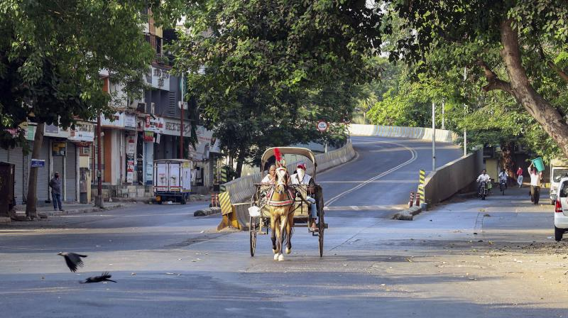 A horse cart carrying passengers is seen on a deserted street during a nationwide lockdown, imposed in the wake of coronavirus pandemic, in Thane. PTI Photo
