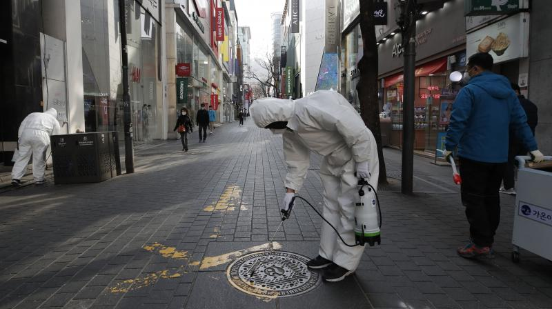 Workers wearing protective gears disinfect as a precaution against the new coronavirus at a shopping district in Seoul, South Korea