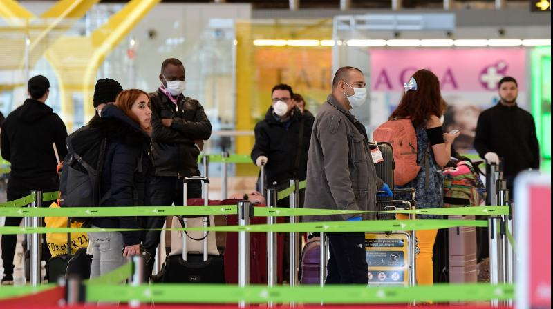 Passengers wearing face masks as a preventive measure queue to do the check-in at the Madrid-Barajas Adolfo Suarez Airport in Barajas. AFP Photo