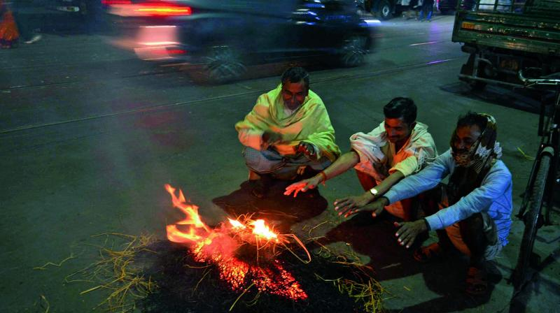 People try to keep themselves warm in the city as cold spell continue in the state. (Photo: Asian Age)