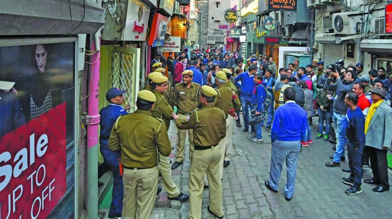 Police personnel outside shops in Khan Market on Monday. The NDMC on Monday sealed many shops in the upscale market for flouting civic norms. (Photo: PTI)