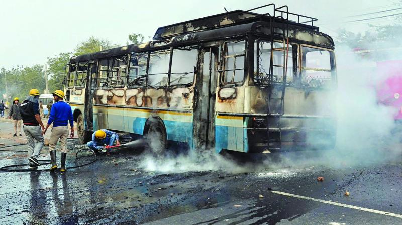 Firefighters and policemen try to douse a fire after activists of the Karni Sena torched a Haryana Roadways bus during a demonstration against the release of Padmaavat in Gurgaon. (Photo: PTI)
