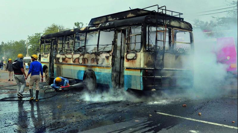 Firefighters try to douse a fire after alleged activists of the Karni Sena torched a Haryana Roadways bus at NH-248 during a demonstration against the release of Padmaavat in Gurgaon recently. (Photo: PTI)