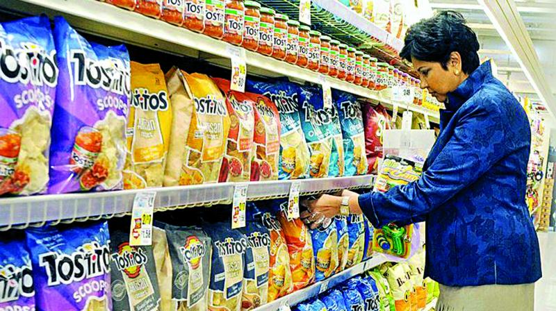 Indra Nooyi inspects a shelf of chips.
