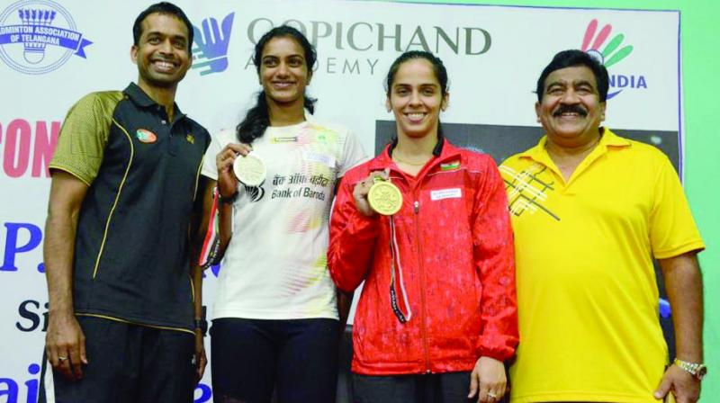 Coach Pullela Gopichand (left) is all smiles as P. V. Sindhu and Saina Nehwal with their silver and bronze medals during a media interaction at the Pullela Gopichand Academy in Hyderabad on Thursday. (Photo:DC)