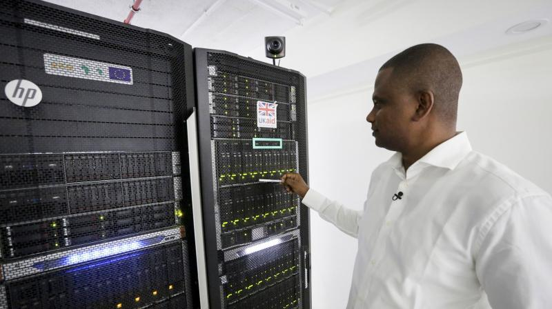 In this photo taken on Thursday, March 5, 2020, Abubakr Salih Babiker, a climate scientist at the Intergovernmental Authority on Development's Climate Prediction and Applications Center, shows server racks containing a supercomputer in Nairobi, Kenya. A supercomputer is boosting efforts in East Africa to control a locust outbreak that raises what the U.N. food agency calls
