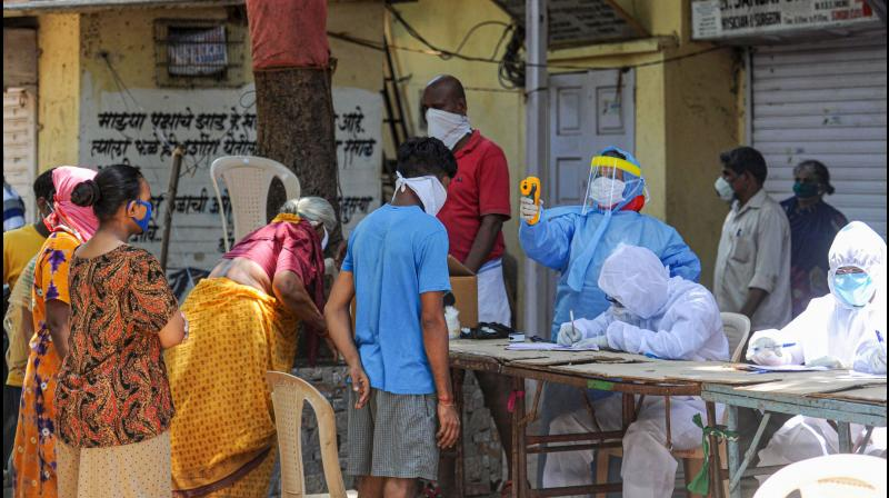 Medics conduct COVID-19 screening of residents at a camp, during the ongoing nationwide lockdown to curb the spread of coronavirus, at Dharavi in Mumbai. (PTI Photo)