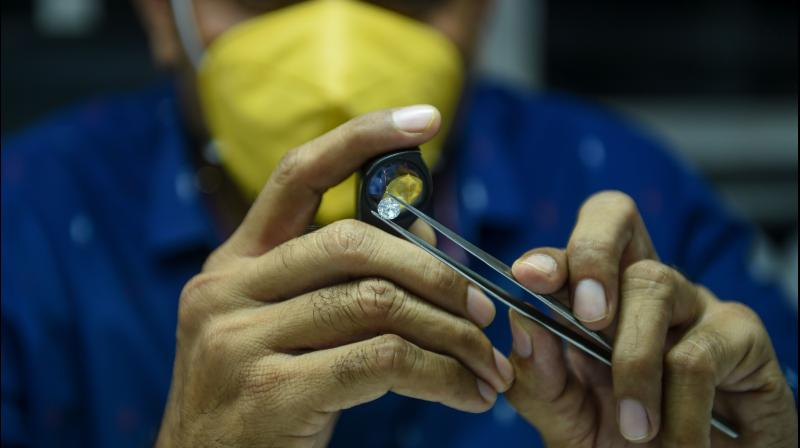 A worker examines diamond stones at Rijiya Gems, a diamond cutting and polishing workshop. (AFP Photo)