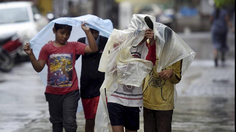 Children cover themselves with raincoats as they walk during rainfall, at Mahim in Mumbai. (PTI Photo)