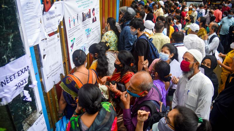 Students with their parents, arrive to appear for NEET exam at Thakur College at Kandivali, in Mumbai. (PTI Photo)
