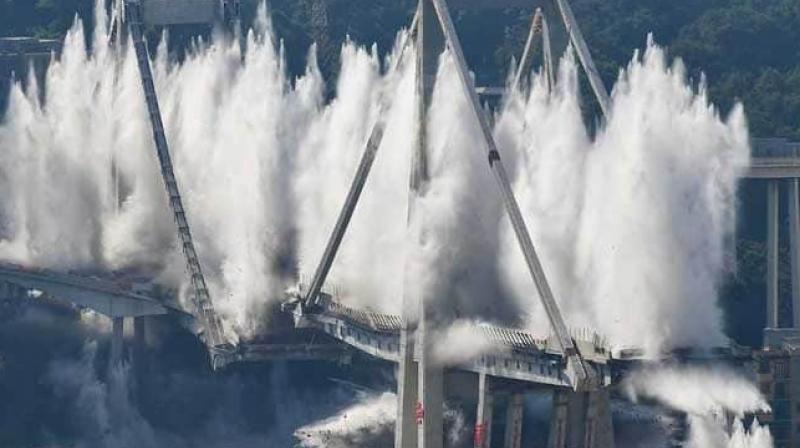 Explosive charges blow up the eastern pylons of Genoa's Morandi motorway bridge. (Photo: AFP)
