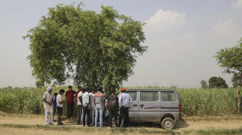 Villagers gather near a crime scene in a field near Jewar. (Photo: AP)