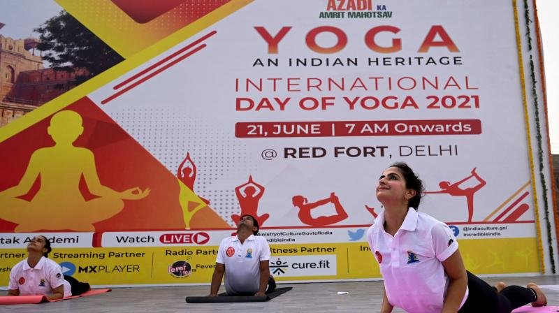 Practitioners perform a yoga position during an event to mark International Yoga Day at the Red Fort in New Delhi. (Photo: PTI)