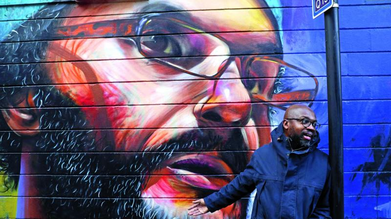 Street muralist, British-Ghanaian artist, Neequaye Dreph Dsane stands beside his artwork, a portrait of British-Moroccan artist, Hassan Hajjaj in a street in east London.