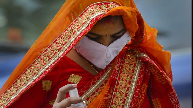 A woman wearing a face mask made from cloth sanitises her hand before boarding a train in Nizamuddin, New Delhi. PTI
