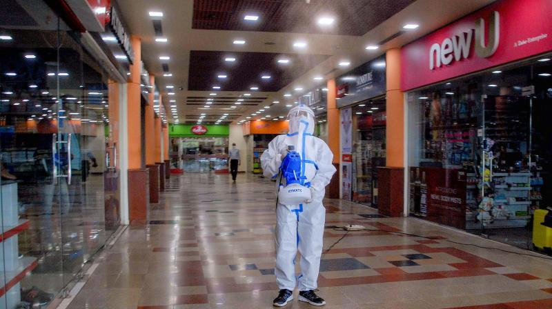 A worker sanitizes a mall ahead of its reopening in Noida on Sunday. PTI photo