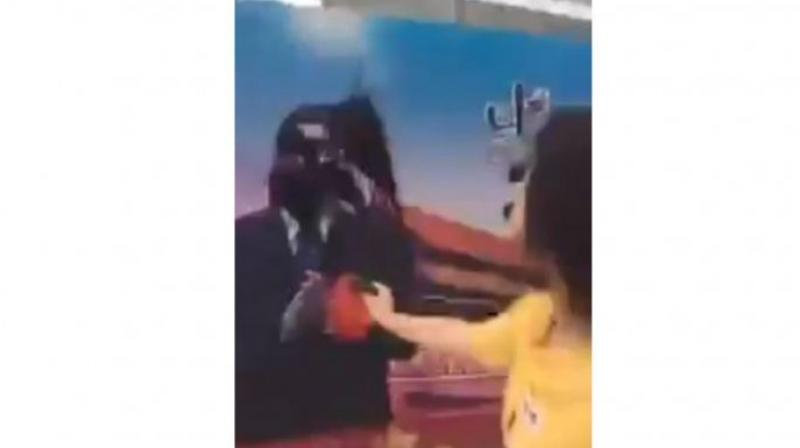 In the video, Dong Yaoqiong splashes ink on a poster bearing President Xi's image at a location in Shanghai's financial district, saying defiantly: 'Xi Jinping, I'm right here waiting for you to arrest me.'  (Photo: Screengrab from Twitter/Huayong798)