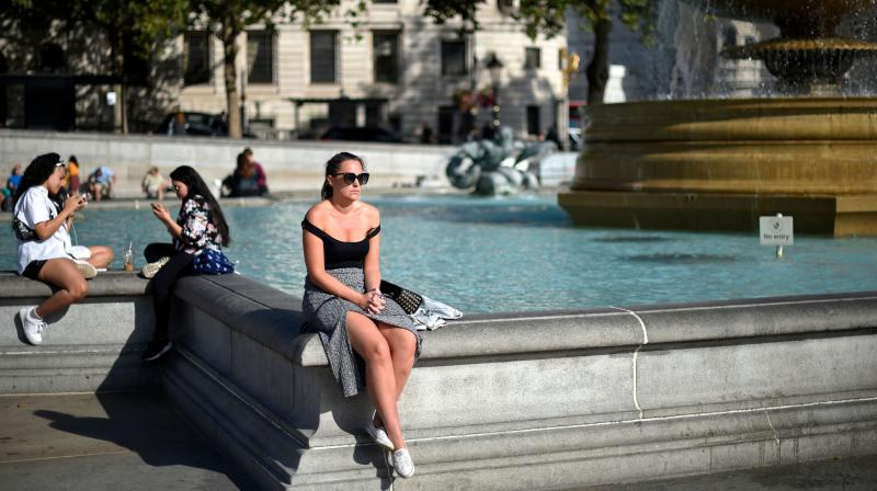 People sunbathe around the fountains in trafalgar Square in central London on September 18, 2020, as the fine weather in the south of England continues. (AFP)