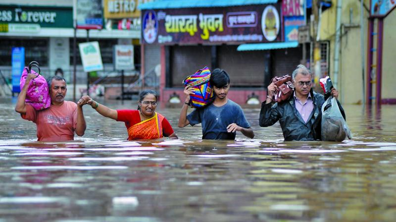 People wade through floodwaters in Sangli. (Photo: PTI)