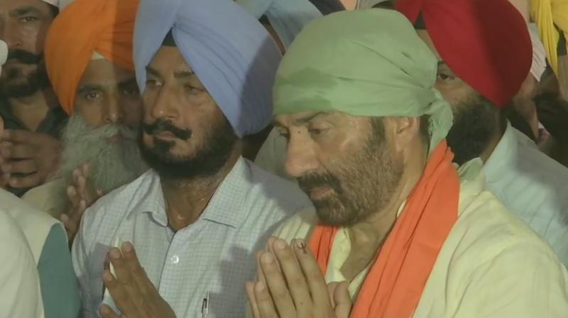 Accompanied by BJP leader Kamal Sharma, Deol offered prayers at the Gurdwara Dera Baba Nanak and had a glimpse of the Gurudwara Kartarpur Sahib in Narowal district of Pakistan through binoculars installed at 'darshan sthal' here. (Photo: ANI twitter)