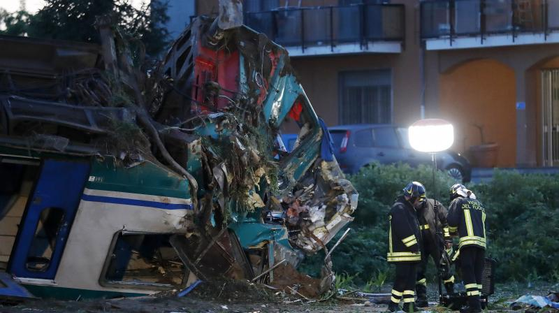 Firemen work next to the twisted wreckage of a train that plowed into a big-rig truck in Caluso, outside Turin, Italy, early Thursday. (Photo: AP)