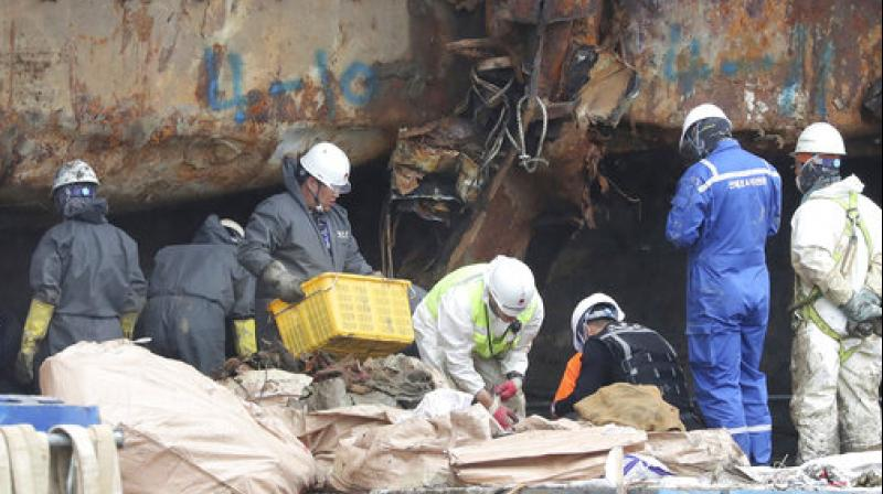 Workers search for bone fragments from the wreckage of the salvaged ferry Sewol at a port in Mokpo, South Korea. (Photo: AP)