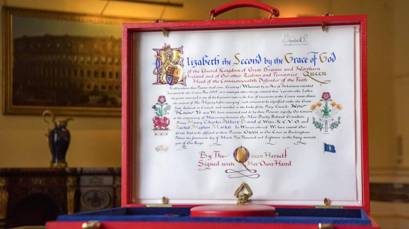 The design to the left of the text incorporates the red dragon of Wales along with the UK's floral emblems. It also includes three tiny red escallops from the Spencer family Arms, the family of Harry's mother, the late Princess Diana. (Photo: AP)