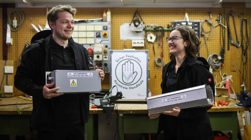 Working student Leon Rottmann and Katharina Obladen (R) stand at the mechanic's workshop of the Startup UVIS UV-Innovative Solutions in Cologne, western Germany, on April 22, 2020. Three blue-glowing UVC lamps line the inside of the rectangular metal case. (Photo   AFP)
