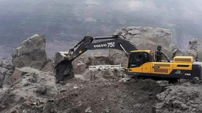 An excavator machine at work during the rescue operations at a coal mine, where several workers were trapped, in Godda, Jharkhand on Friday. (Photo: PTI)