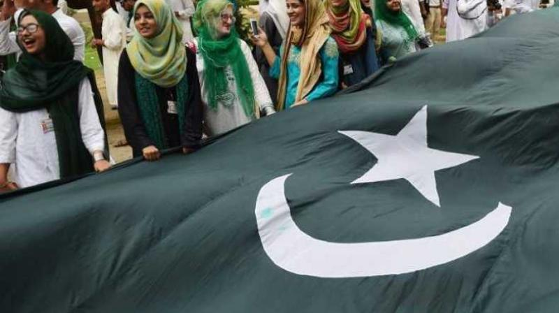 University of Karachi students celebrate with a large national flag ahead of the upcoming Independence Day in Karachi on August 13, 2018. (Photo: AFP)
