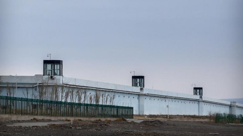 People stand in a guard tower on the perimeter wall of the Urumqi No. 3 Detention Center in Dabancheng in western China's Xinjiang Uyghur Autonomous Region on April 23, 2021. China's largest detention center is twice the size of Vatican City and has room for at least 10,000 inmates. (AP Photo)