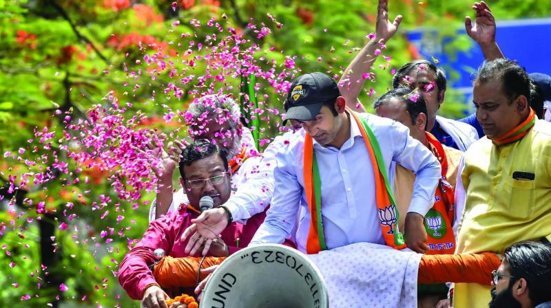BJP East Delhi candidate Gautam Gambhir waves at his supporters during a rally on Friday. (Photo: PTI)