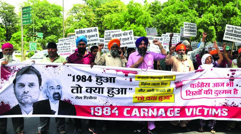 Family members of the 1984 anti-Sikh riot victims shout slogans during a protest against Congress leader Sam Pitroda in New Delhi on Friday. (Photo: BUNNY SMITH)