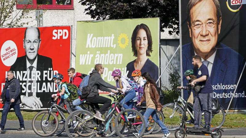 People walk and drive past election posters of the three candidates for German chancellor , from right, Armin Laschet, Christian Democratic Union (CDU), Annalena Baerbock, German Green party (Die Gruenen) and Olaf Scholz, Social Democratic Party (SPD), at a street in Gelsenkirchen, Germany. Germany's closely fought election on Sunday will set the direction of the European Union's most populous country after 16 years under Angela Merkel, whose party is scrambling to avoid defeat by its center-left rivals after a rollercoaster campaign. (AP)