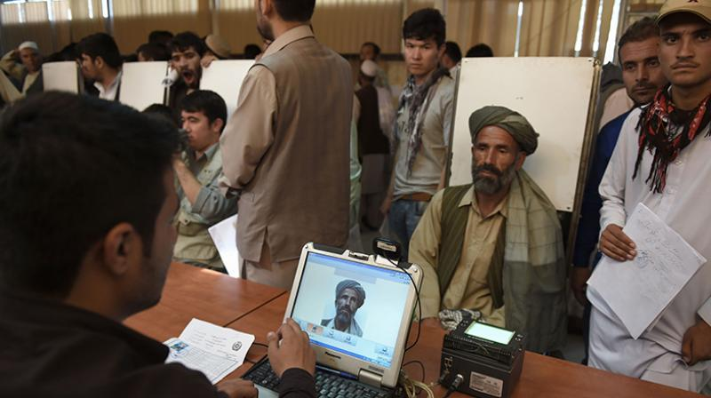 An Afghan man has his photograph taken for facial biometric information as he applies for his passport at the passport office in Kabul. -AFP