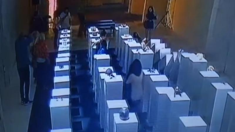 Moment when the woman topples over expensive art is caught on tape (Photo: Youtube)