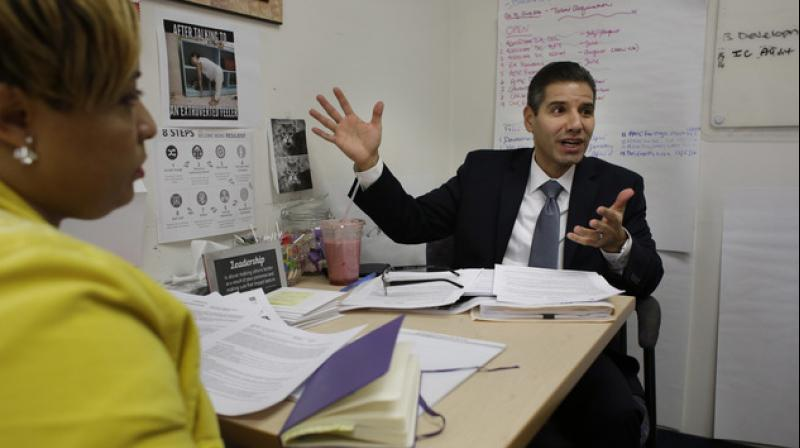 John Valverde speaks during a meeting while seated next to Chiffawn Johnson, a talent acquisition manager and human resources generalist at YouthBuild USA, Inc., in Somerville. (Photo: AP)