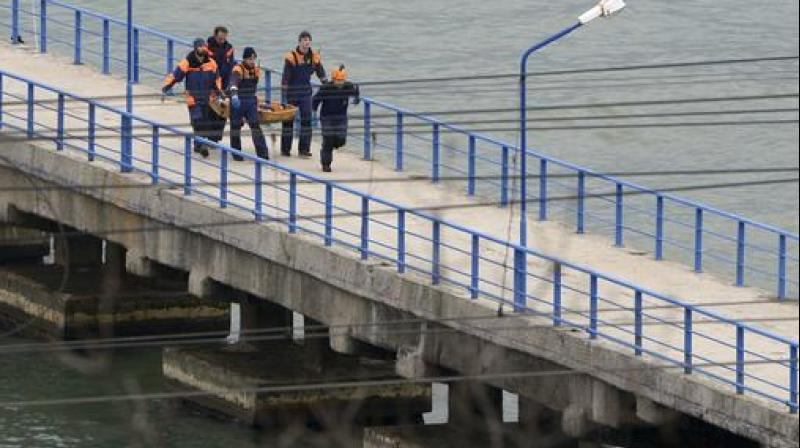 Russian rescue workers carry a body from the wreckage of the crashed plane, at a pier just outside Sochi, Russia. (Photo: AP)