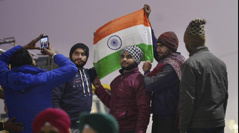 A farmer holds the Tricolor during their ongoing agitation against Centre's farm reform laws, on the eve of Republic Day, in New Delhi, Monday, Jan. 25, 2021. (PTI /Ravi Choudhary)