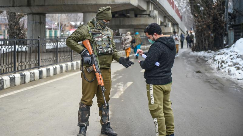 A security personnel checks an identity card of a youngster near the Sher-e-Kashmir Cricket Stadium on the eve of the 72nd Republic Day function in Srinagar, Monday, January 25, 2021. Security has been beefed up across Jammu and Kashmir ahead of R-Day (PTI/S. Irfan)