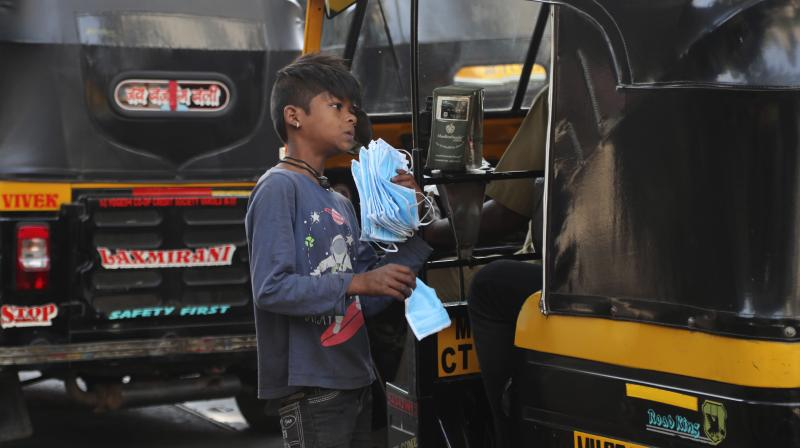 A boy sells face masks at a traffic intersection in Mumbai on March 15, 2020. (AP)