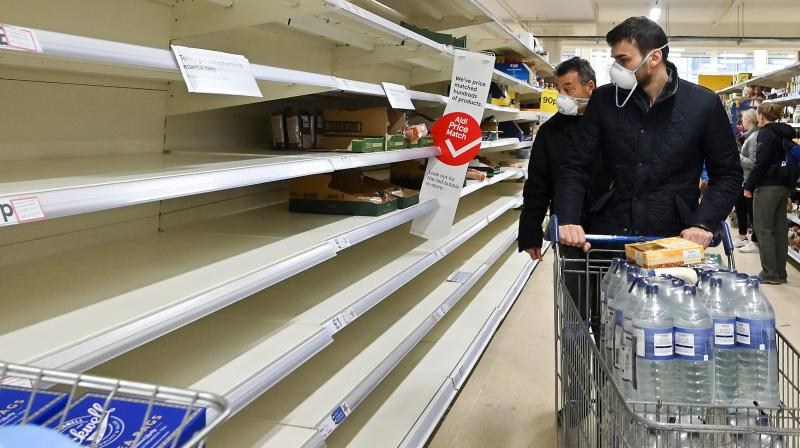 Shoppers wearing masks are faced with partially empty shelves at a supermarket in London on March 14, 2020, as consumers worry about product shortages, leading to the stockpiling of household products due to the outbreak of the novel coronavirus COVID-19.  Faced with supermarkets being emptied and online shopping overrun due to the COVID-19 pandemic, UK retailers are appealing to consumers to come to their senses and ensure that the country will not run out of food. (AFP)