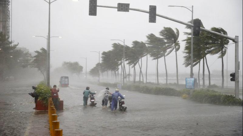 Motorists brave rain and strong winds brought about by Typhoon Mangkhut. (Photo: AP)