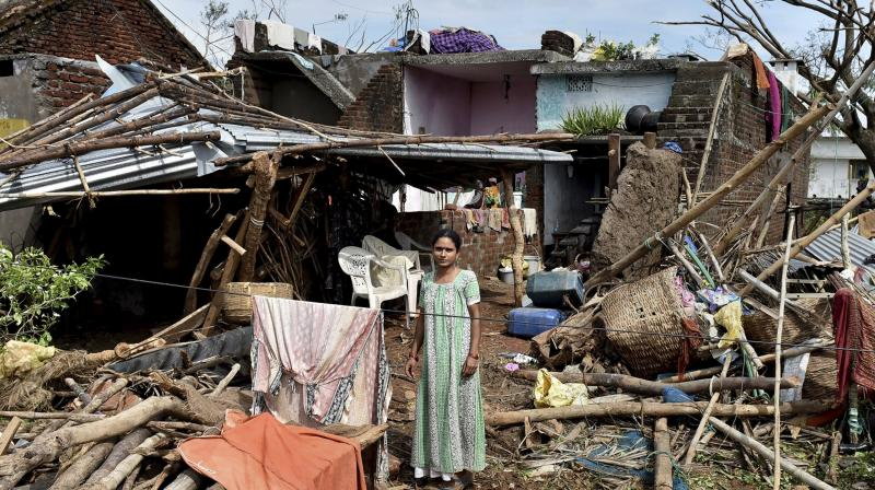 A woman stands near her damaged house hit by cyclone 'Titli' on Friday, October 12, 2018. (Photo: PTI)
