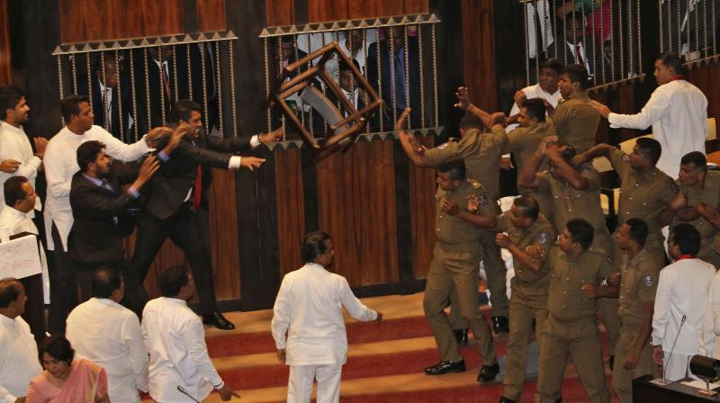 Lawmakers supporting disputed Prime Minister Rajapksa throw a chair towards police officers escorting the speaker inside parliament in Colombo, Sri Lanka, Friday, November 16, 2018. (Photo: AP)
