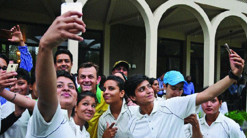 Girls from Delhi University and Jammu and Kashmir's CM XI team click selfies with Adam Gilchrist.
