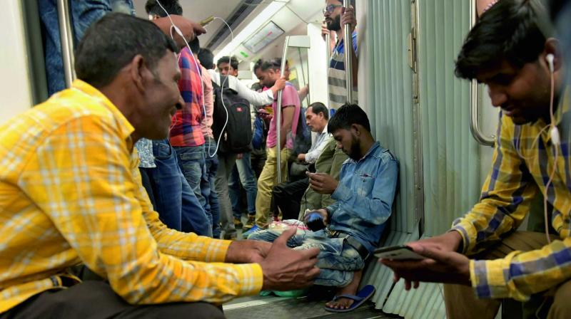 Commuters inside a Delhi Metro carriage leaning in the coach junction area. (Photo: PTI)