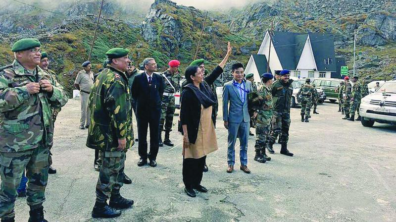 Defence minister Nirmala Sitharaman acknowledges a row of Chinese soldiers from across the fence who were taking pictures on her arrival at Nathu La. (Photo: PTI)