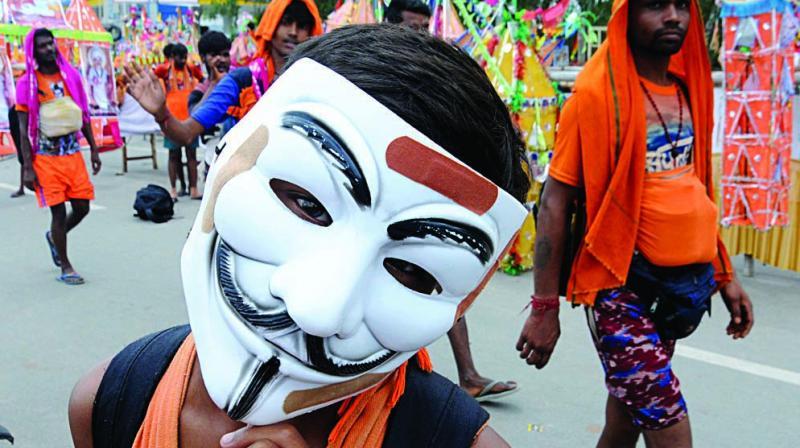 A kanwariya wears mask during the annual yatra in New Delhi on Monday. (Photo: G.N. JHA)