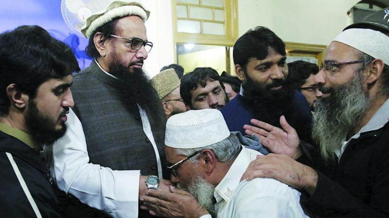 Supporters of Hafiz Saeed (second from left), head of Jamaat-ud-Dawa, kiss his hands as he arrives after his release at a mosque in Lahore. (Photo: AP)